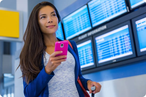 Asian female checking flight at airport on mobile